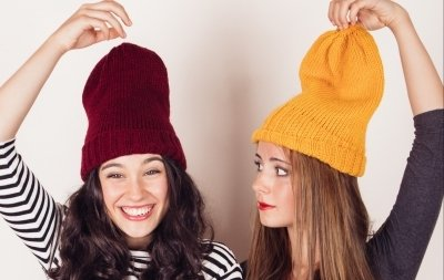 Funny and crazy girl friends with wool caps celebrating autumn or winter