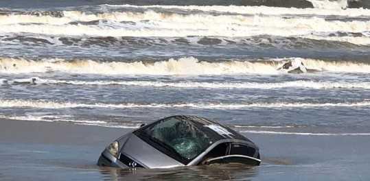 Mar agitado dificulta retirada de carro atolado na beira do mar, em Capão da Canoa